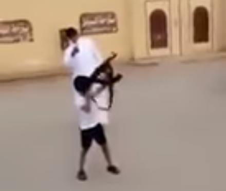 """شخص يحفز طفل على إطلاق النار من """"رشاش"""".. والشرطة تضبطه (فيديو)"""